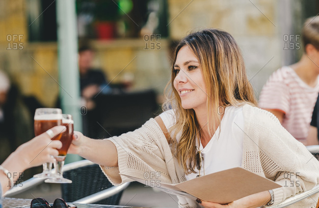 Attractive stylish woman with glass of refreshing beer sitting in cafe and clinking with friend