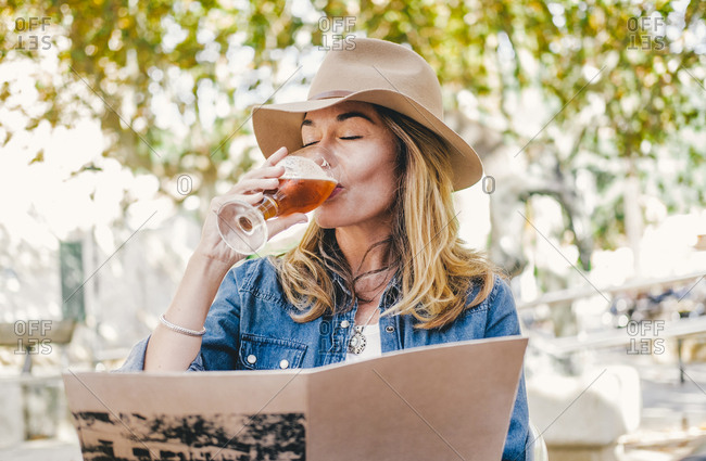 Attractive stylish woman with glass of refreshing beer sitting in cafe reading the menu