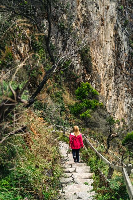 Woman walking down on stone steps leading down to foamy sea