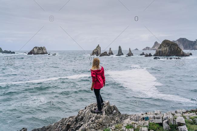 Woman on stony seashore looking on foamy water washing peaks