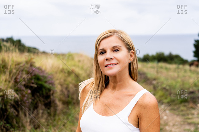 Inspired blonde woman with charming smile looking at camera while enjoying of views of countryside around