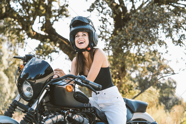 Side view of serious attractive woman in helmet sitting on shiny clean motorbike in park