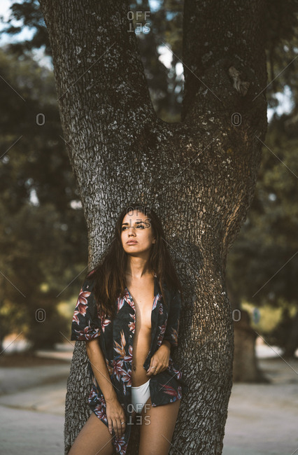 Sensual attractive woman in Hawaiian shirt and white panties contemplating and standing by old tree at park
