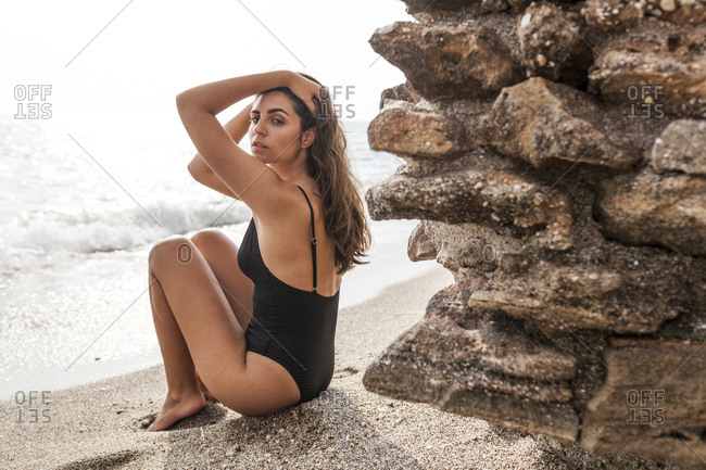 Side view of attractive pensive woman in black swimwear relaxing on seashore sitting by stone wall and looking at camera