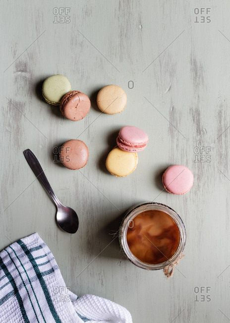 Top view of dessert spoon and cotton towel placed near cup of fresh coffee and colorful macaroons on white table