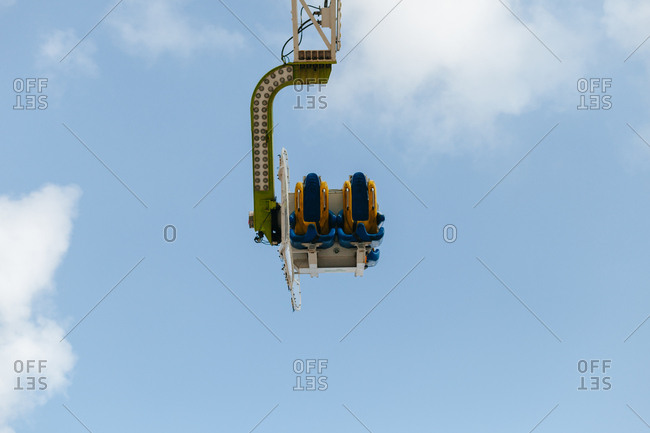 From below of empty booth of modern carousel riding over blue cloudy sky