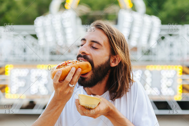 Delighted bearded man biting sandwich with closed eyes while standing beside lighted attraction at carnival