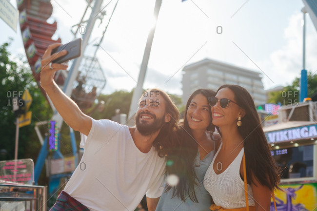 Cheerful smiling tanned people taking photo on smartphone while standing next to attraction at carnival
