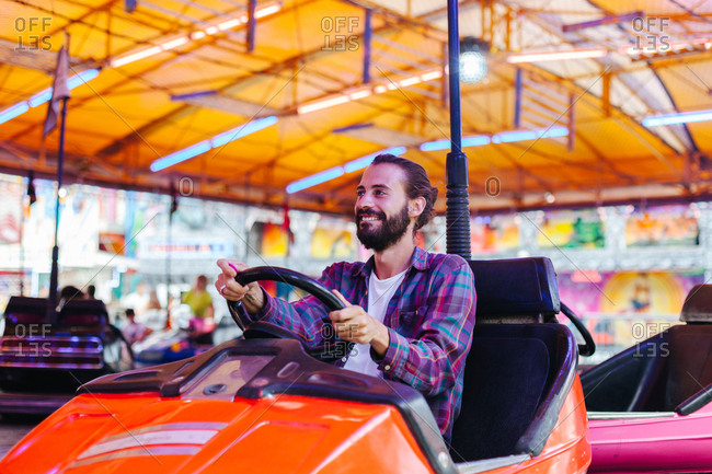 Joyful smiling man in casual clothes having fun and driving colorful attraction car at fairground