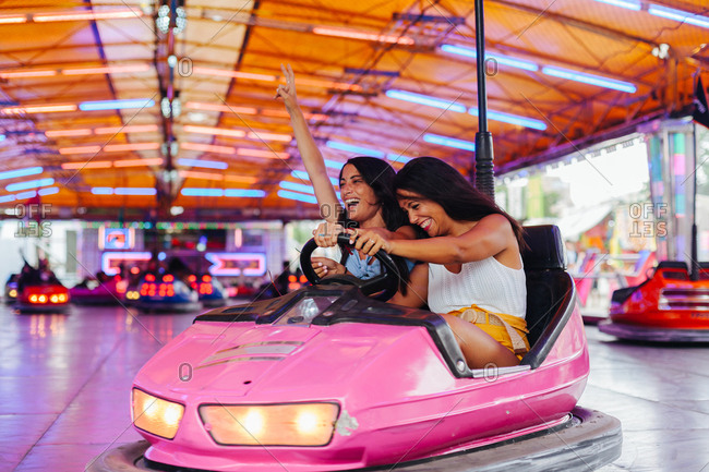 Cheerful women in casual outfit having fun and driving colorful attraction car at carnival