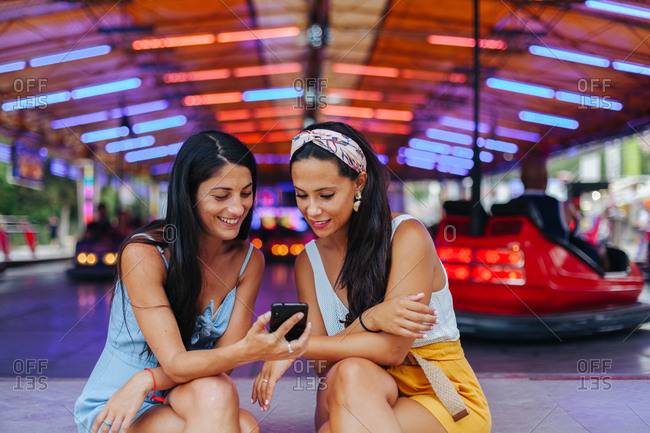 Content smiling tanned women taking photo on smartphone while sitting next to amusement attraction at carnival
