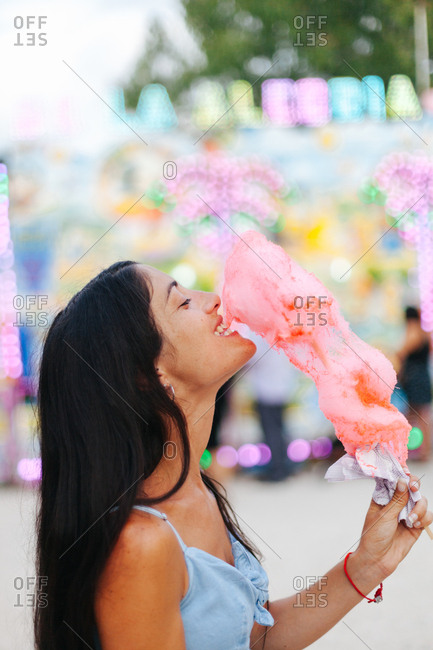 Side view of charming smiling brunette biting cotton candy while standing next to multicolored attraction with neon lights at funfair
