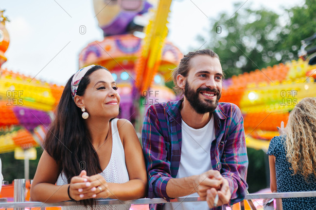 Amused casual couple looking up in excitement while visiting colorful attraction at sunny funfair