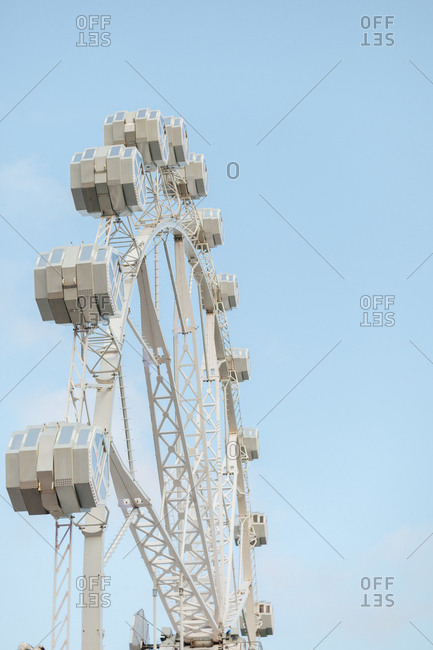 Low angle of section of modern observation wheel at amusement park and blue sky