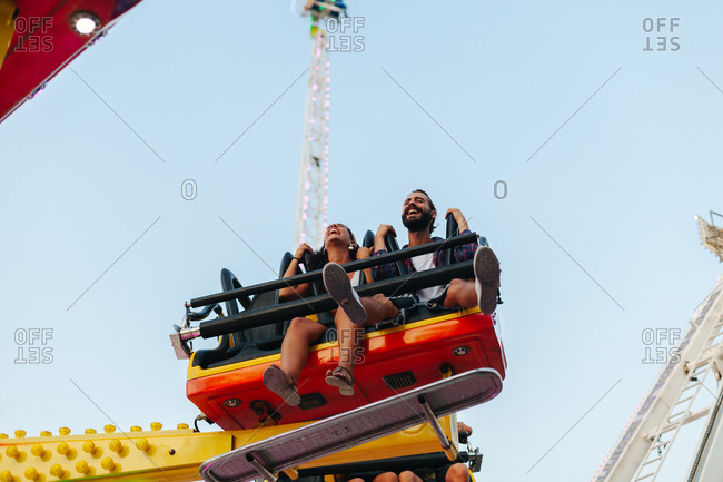 Enthusiastic carefree woman and man having fun while enjoying ride at colorful attraction at sunny funfair
