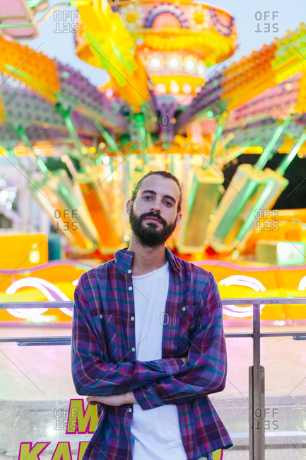 Calm hipster man in casual clothes standing with crossed arms beside lighted colorful carousel at fairground