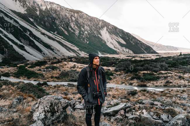 Peaceful man in warm clothes with camera contemplating while standing by rural road at scenic mountain valley