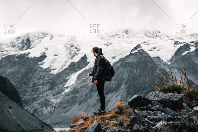 Peaceful man in warm clothes with camera looking away while standing by rural road at scenic mountain valley contemplating