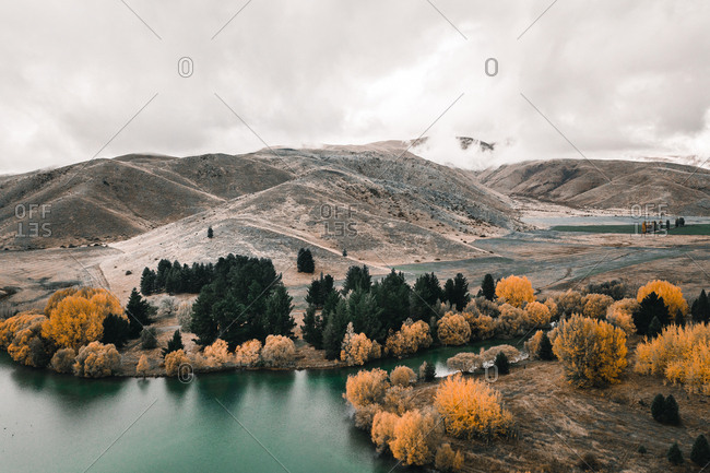 Peaceful mountain lake surrounded with hills and bright trees with orange foliage on misty day