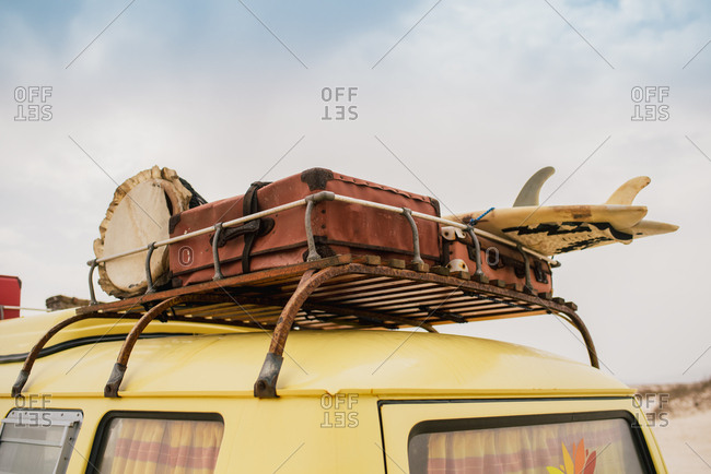 Rusty baggage rack of yellow car loaded with vintage suitcases and surfboard