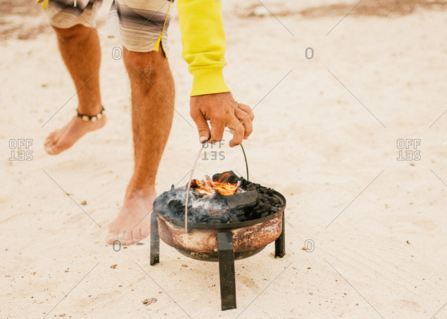 Tanned man cooking on camping stove beside parked mini van