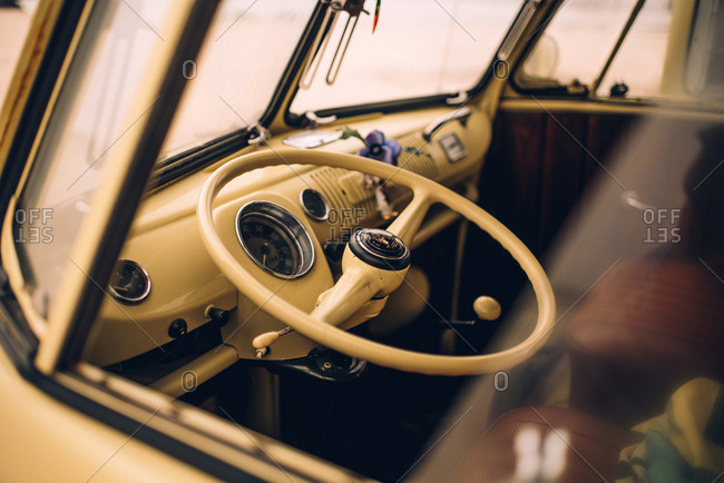 Driving wheel of retro yellow car in empty cabin through window glass