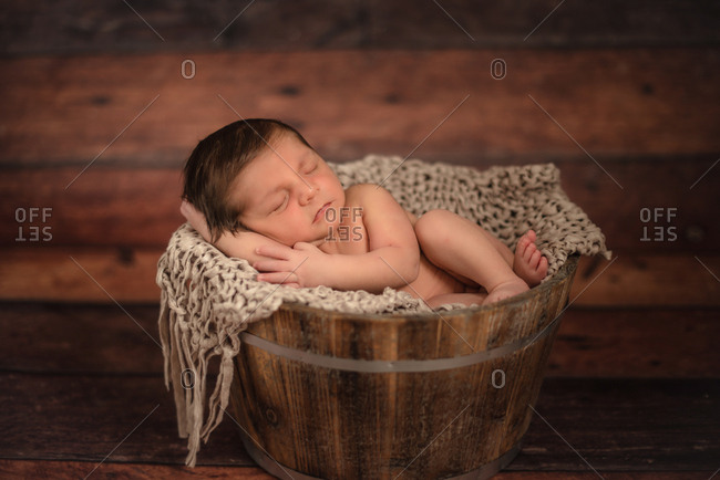 nude infant in bucket on wooden floor at home