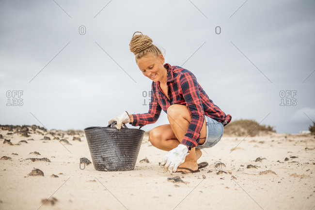 Positive hipster woman in casual clothes and gloves collecting trash into bag while squatting on deserted beach