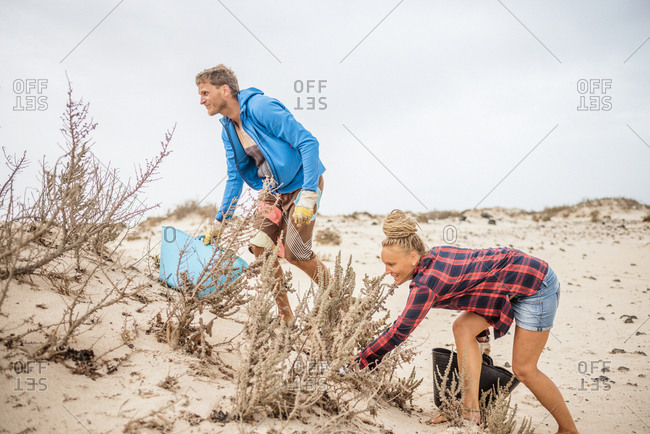 Positive hipster woman and man in casual clothes and gloves collecting trash into bag while squatting on deserted beach