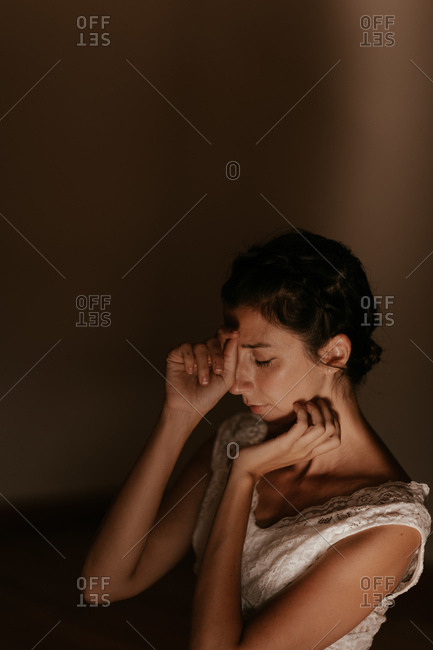 Side view of slim young female with closed eyes crossing and praying against brown wall in church