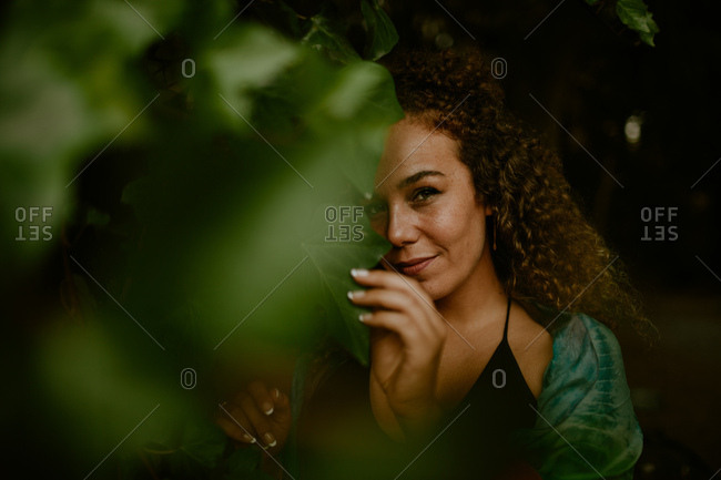 Adult lady with curly hair touching green vine leaves and looking at camera with smile while spending time in dark forest