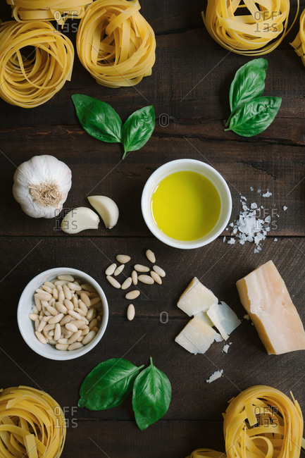Top view of fresh herbs and cheese with oil and tagliatelle pasta arrange in rustic wooden table