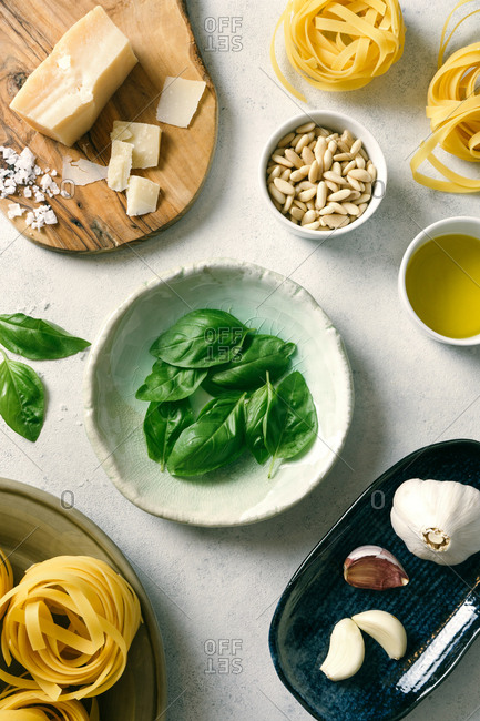 Basil leaves and ingredients for pesto sauce on plates on table