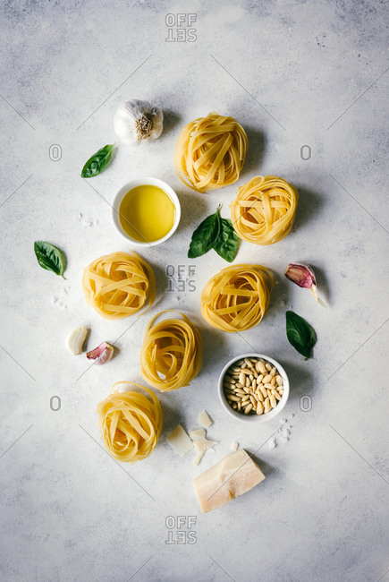 Nests of tagliatelle pasta with basil leaves and garlic on table