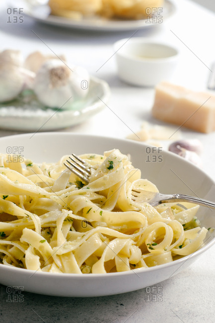 Cooked tagliatelle pasta with pesto sauce on fork