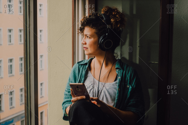 Pensive curly woman in headphones listening to music while browsing smartphone and sitting on window sill in apartment looking out of the window