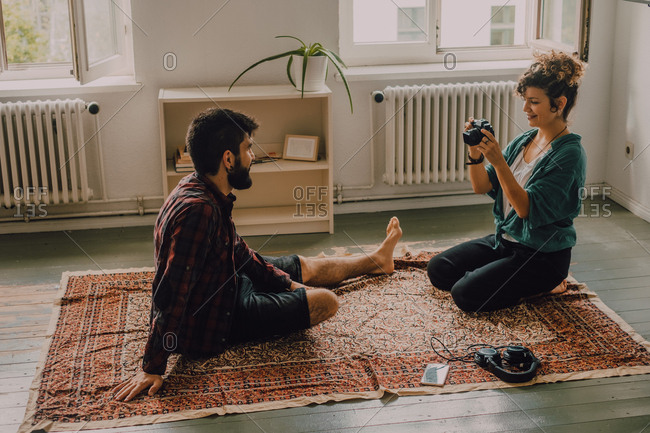 Side view of hipster woman taking picture of man sitting barefoot and posing on apartment floor