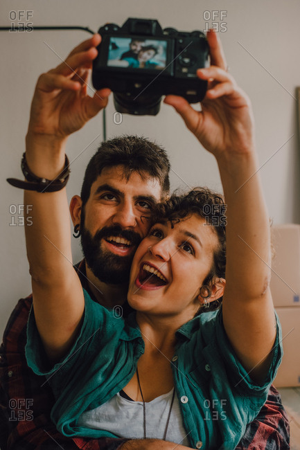 Affectionate hipster couple hugging and taking selfie with photo on camera while sitting on floor at home