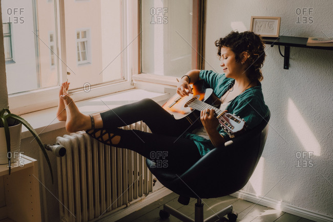 Relaxed barefoot woman in casual clothes playing acoustic guitar while sitting on chair next to window at home