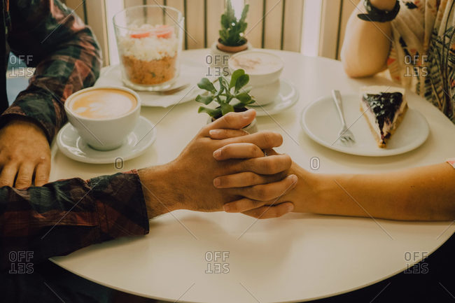 Close-up view of anonymous affectionate couple in casual clothes holding hands while sitting at table in cafe