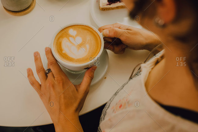 First person view of woman holding mug while sitting in modern coffee shop