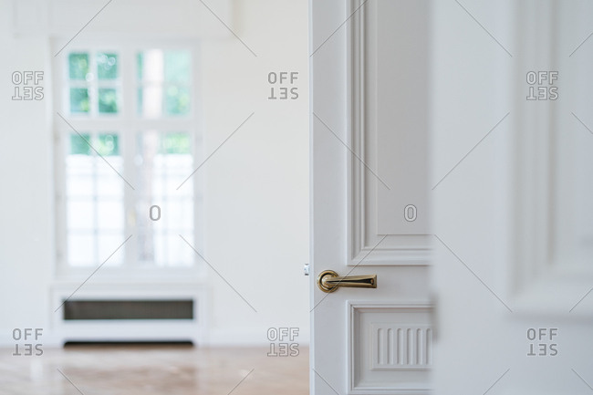 Open white door with golden handle in light minimalist interior on blurred background