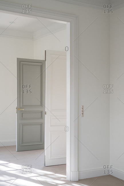 Open bicolor swing door with modern handle in white minimalistic interior