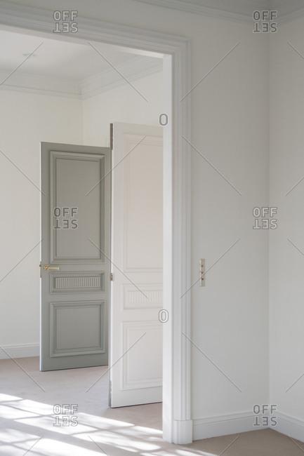 Open bicolor swing door with modern handle in white minimalistic interior