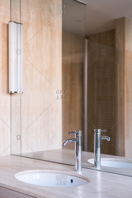 Oval washbasin and shiny steel faucet on wooden stand with mirror in modern bathroom