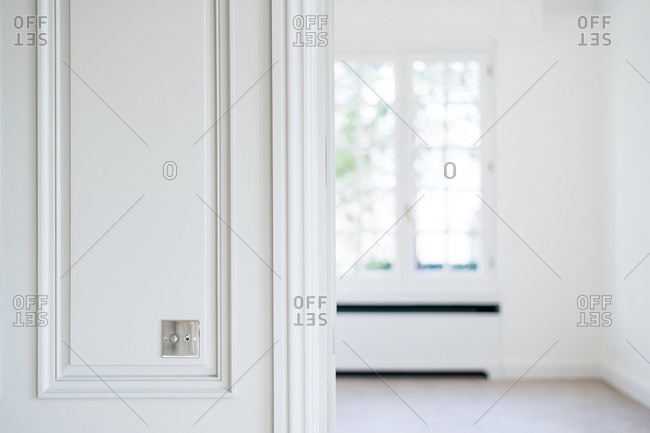 Metal switch on white wall in room with trendy minimalist interior