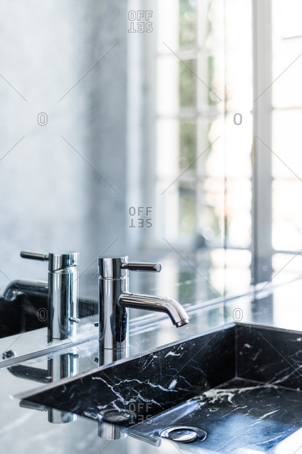 Rectangular washbasin and shiny steel faucet in luxurious bathroom in daylight