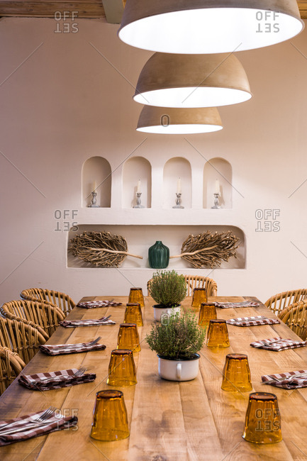 Classic lampshades with warm light hanging over set wooden table in light hall