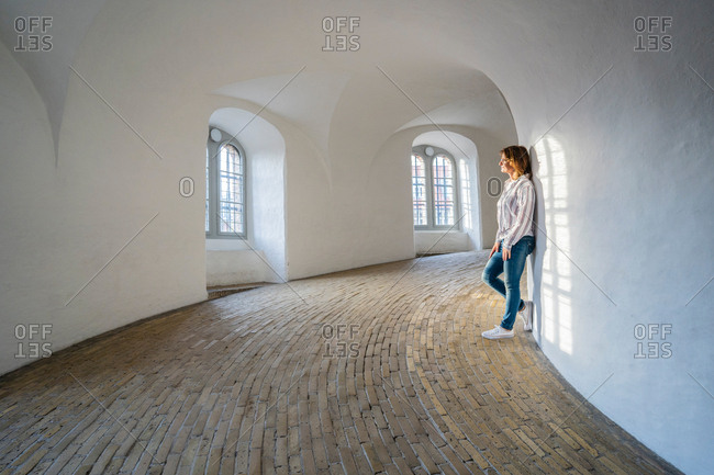 Side view of calm woman in jeans leaning on white wall at minimalistic hall with arched windows