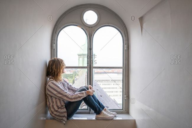 Side view of dreaming modern woman sitting on sill and looking out arched window